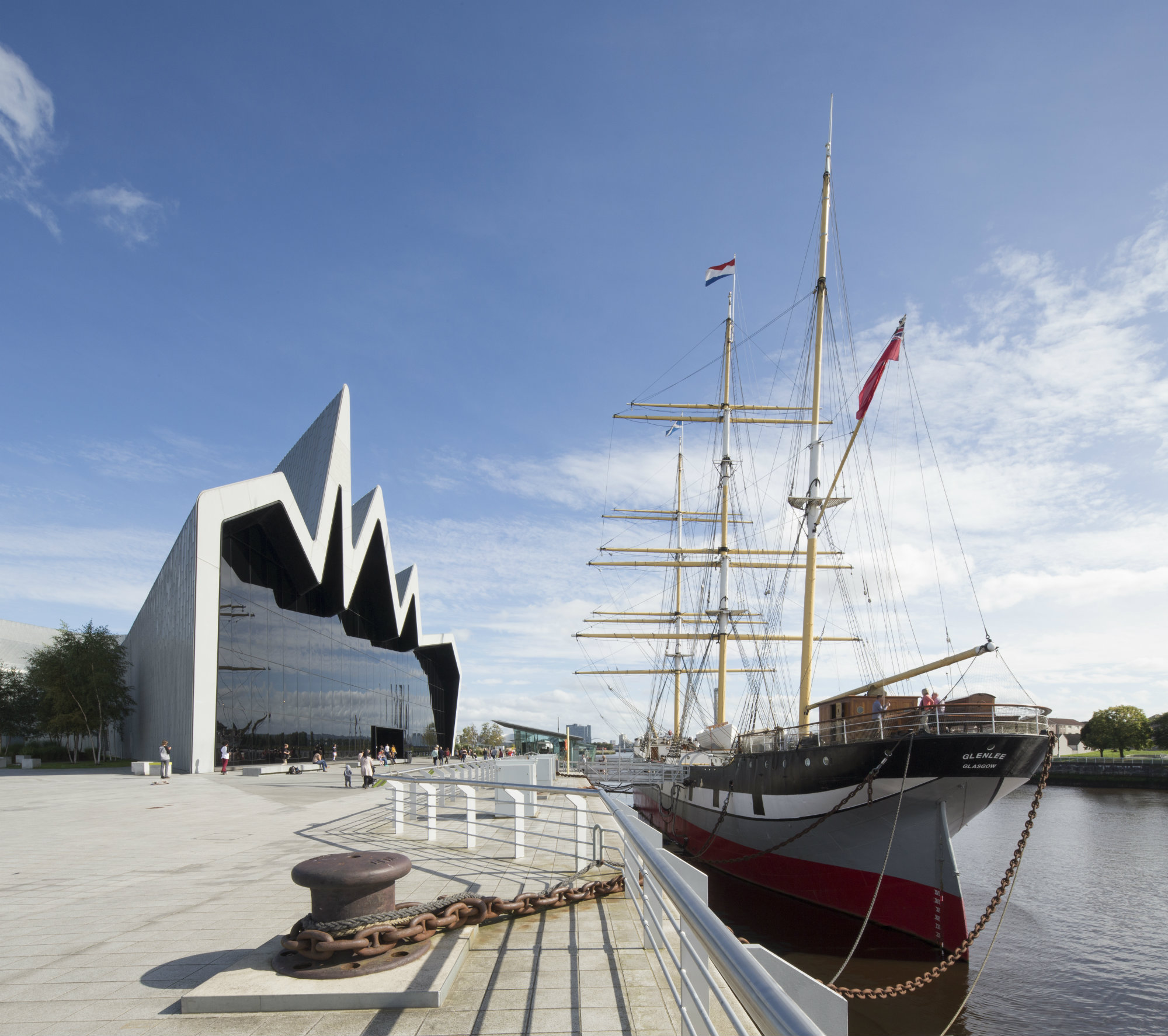 Modern glass and steel with pointed roof and tall ship in foreground