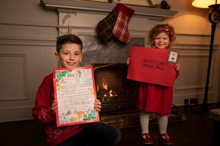 Christmas stocking hanging from a fireplace. Children in foreground holding letters to Santa.